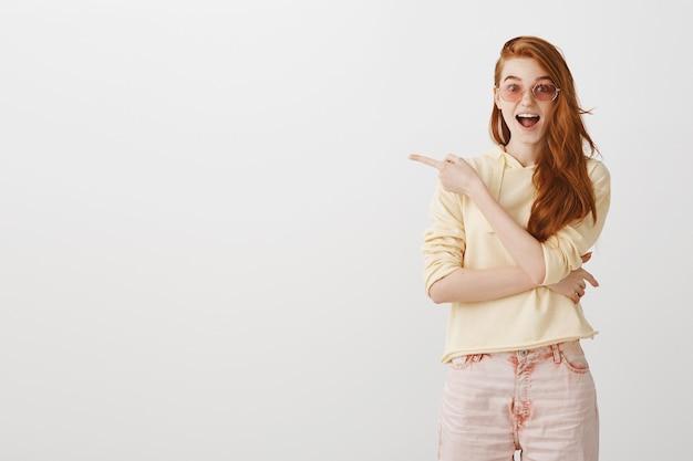 Chica pelirroja emocionada en gafas de sol apuntando con el dedo a la izquierda
