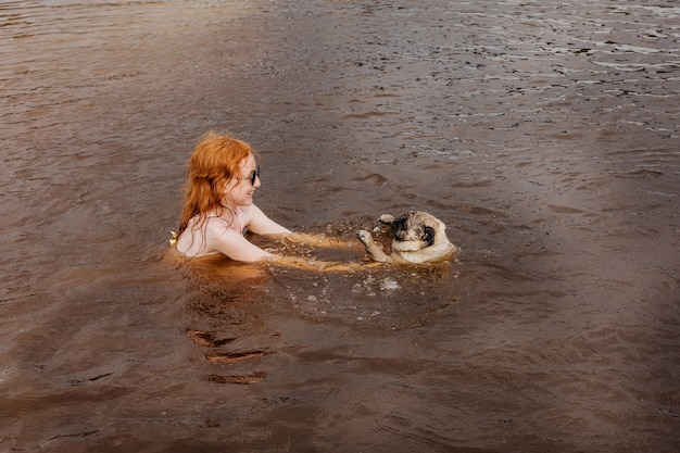 Chica pelirroja le enseña a su pug a nadar en el río.