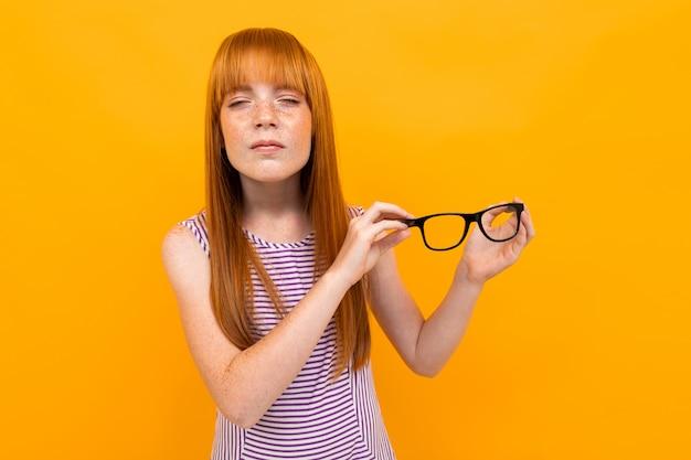 Chica pelirroja entrecerra los ojos con gafas en las manos sobre fondo amarillo
