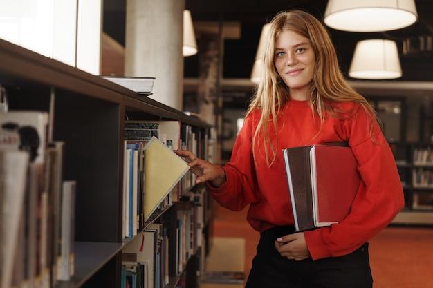Chica pelirroja, estudiante universitaria elige un libro del estante en la biblioteca o librería, sonriendo a la cámara.
