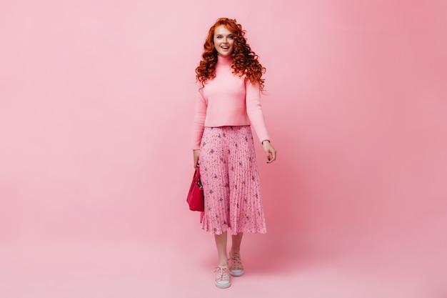 Chica pelirroja en falda rosa y suéter posando con bolsa brillante en pared aislada