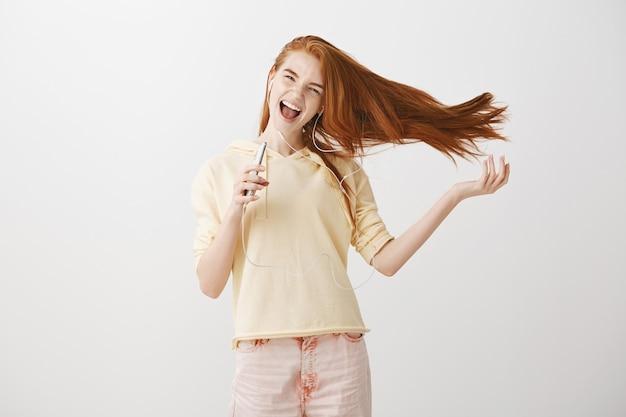 Chica pelirroja feliz jugando el juego de la aplicación de karaoke en el teléfono inteligente, cantando canciones en auriculares