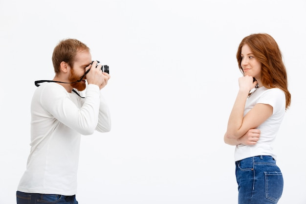 Chica pelirroja fotografiando hombre
