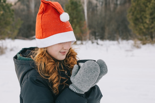 Chica pelirroja con un gorro de papá noel bebiendo té en un paseo de invierno.