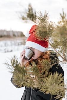 Una chica pelirroja con un gorro de papá noel está bebiendo té entre las ramas de abeto.