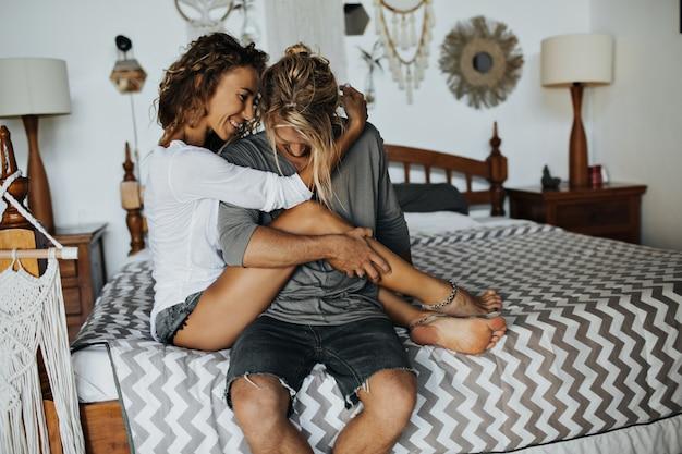 Chica pelirroja con hermosa sonrisa está sentada en manos de un joven que acaricia sus piernas