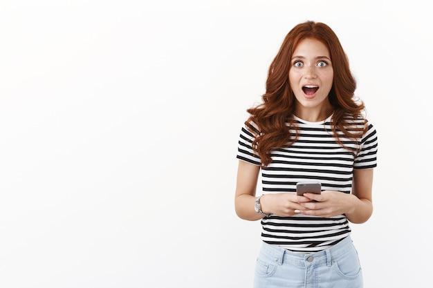 Chica pelirroja impresionada y conmocionada chismeando sobre su actriz favorita después de leer noticias asombrosas en internet, sostener el teléfono inteligente, dejar boquiabierto