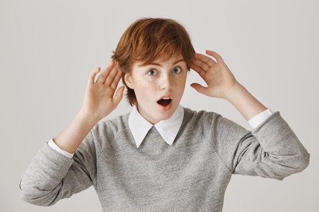 Chica pelirroja intrigada con corte de pelo corto posando contra la pared blanca