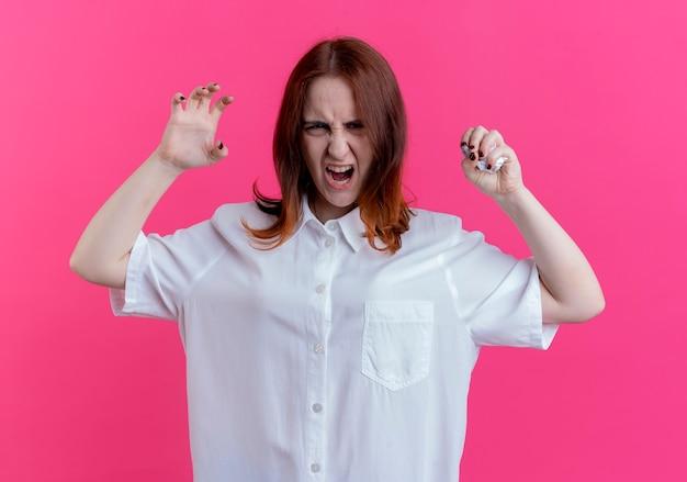 Chica pelirroja joven enojada aplastando papel y haciendo estilo tigre aislado en la pared rosa