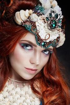 Chica pelirroja con maquillaje brillante y pestañas grandes.