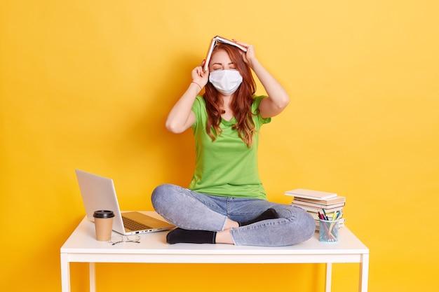 Chica pelirroja con máscara médica se sienta con las piernas cruzadas sobre una mesa blanca con un libro sobre la cabeza, mantiene los ojos cerrados, usa jeans y camiseta verde, rodeada de lap top, café, bolígrafos.