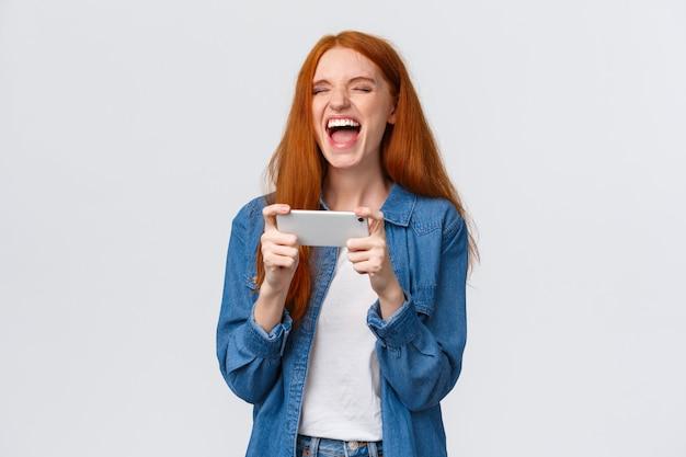 Chica pelirroja milenaria guapa y despreocupada que se divierte, ve el vlogger favorito, se ríe de videos divertidos en línea, sostiene el teléfono inteligente horizontalmente, de pie alegre
