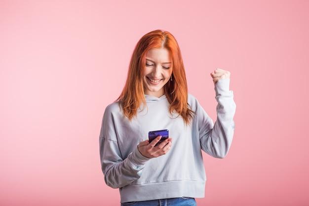 Chica pelirroja mira el teléfono y muestra el gesto del ganador en el estudio sobre un fondo rosa