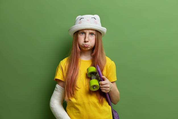 Chica pelirroja molesta con el brazo dañado después de andar en patineta, tiene fractura, mueca hosca, cabello largo rojo, vestida con ropa de verano, aislada en la pared verde. deporte extremo, niños, estilo de vida.