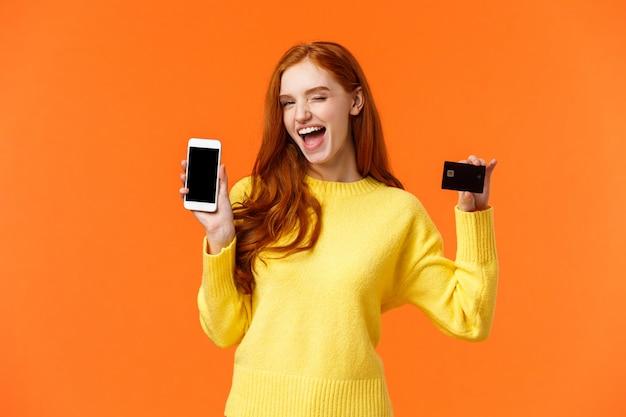 Chica pelirroja mostrando teléfono inteligente y tarjeta de crédito, guiño y sonrisa cámara, promover banca en línea, depósito o método de pago