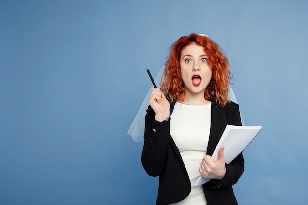 Chica pelirroja, la novia está sosteniendo un cuaderno para notas con una mirada pensativa, planeando su negocio. planificador de la boda.