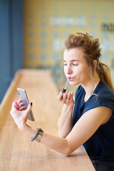 Chica pelirroja poniéndose lápiz labial sola, mirando el reflejo en el teléfono inteligente