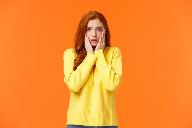 Chica pelirroja preocupada y ansiosa se agarra la cara, jadeando asustada y preocupada, no sé qué hacer, parada tensa y asustada.