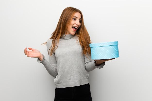 Chica pelirroja sobre pared blanca con caja de regalo en manos