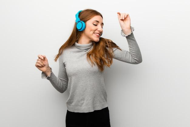 Chica pelirroja sobre pared blanca escuchando música con auriculares y bailando