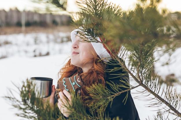 Chica pelirroja con un sombrero de santa claus en un paseo de invierno bebiendo té con pan de jengibre.