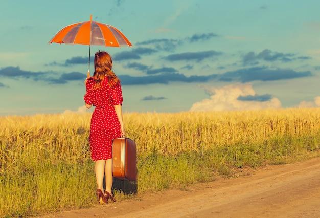Chica pelirroja con sombrilla y maleta al aire libre