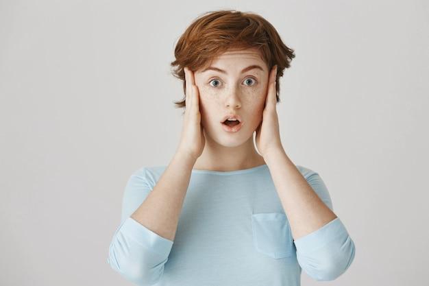 Chica pelirroja sorprendida y conmocionada posando contra la pared blanca