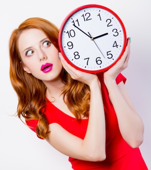 Chica pelirroja sorprendida en vestido rojo con gran reloj en blanco