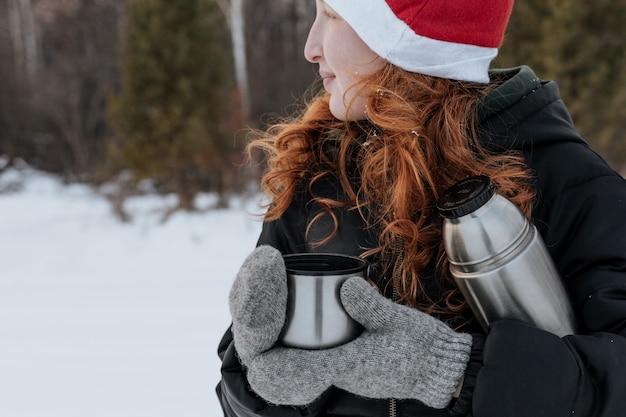 Chica pelirroja con termo bebe té en un paseo de invierno.
