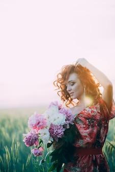 Chica pelirroja en vestido rojo con ramo de flores de peonías en el campo de trigo de verano al atardecer. resplandor solar.
