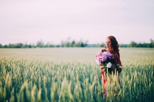 Chica pelirroja en vestido rojo con ramo de flores de peonías en el campo de trigo de verano al atardecer.