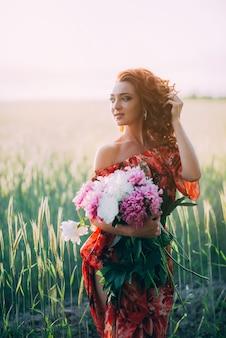 Chica pelirroja en vestido rojo con ramo de flores de peonías campo en verano al atardecer. la felicidad de la mujer.