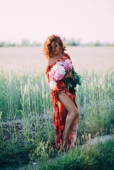 Chica pelirroja en vestido rojo con ramo de peonías bailando alegre en campo de trigo en verano al atardecer. vertical