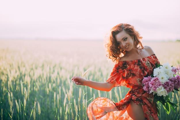 Chica pelirroja en vestido rojo con ramo de peonías bailando alegre en campo de trigo en verano al atardecer.