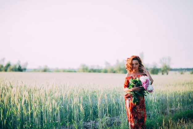 Chica pelirroja en vestido rojo con ramo de peonías caminando por el sendero en el campo de verano al atardecer.
