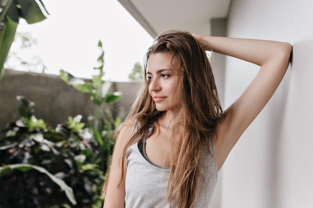 Chica de pelo castaño posando con expresión de cara soñadora junto a la pared blanca. señora caucásica pensativa tocando su pelo largo y mirando a otro lado.
