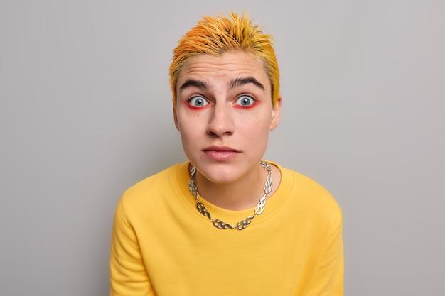 Chica con pelo corto amarillo brillante maquillaje mira sorprendida vestida casualmente reacciona en asombrosa relevación en gris