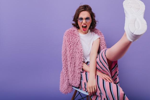 Chica de pelo corto emocional en zapatos blancos sentada en la pared púrpura. adorable jovencita en chaqueta de piel gritando mientras posa en la silla.