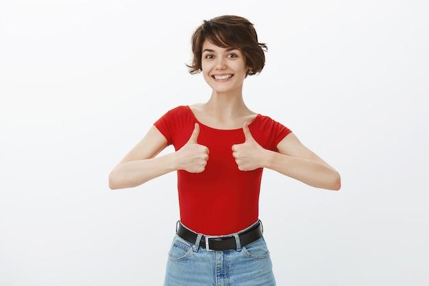 Chica de pelo corto posando en camiseta roja
