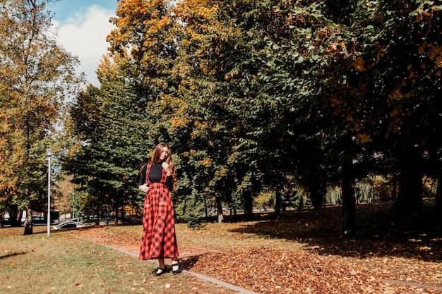 Chica con el pelo largo y castaño en el parque de otoño chica con vestido largo escocés rojo