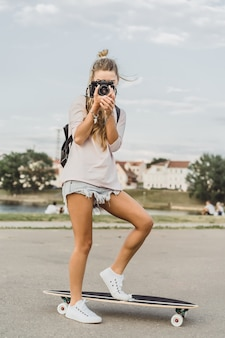 Chica con el pelo largo con monopatín fotografiando en cámara. calle, deportes activos