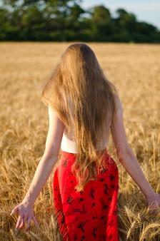 Chica con el pelo largo de pie en un campo de trigo con la espalda, a los rayos del sol de la tarde