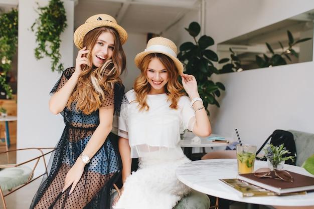 Chica de pelo largo en reloj de pulsera de moda posando juguetonamente junto a la hermana durante el descanso en el restaurante