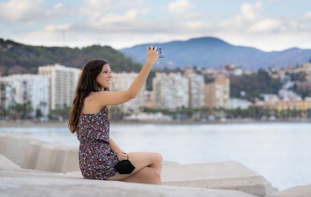 Chica de pelo muy largo con vestido tomar un selfie en el puerto con fondo de mar