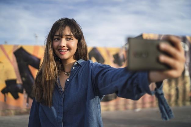 Chica de pelo negro tomando una foto de sí misma detrás de un edificio