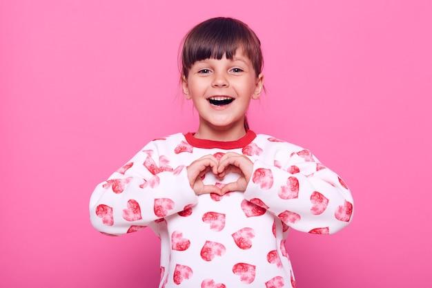 Chica de pelo oscura positiva emocional mirando a cámara con mirada emocionada, mostrando en forma de corazón con los dedos, expresando amor, vistiendo un suéter blanco, aislado sobre una pared rosa.