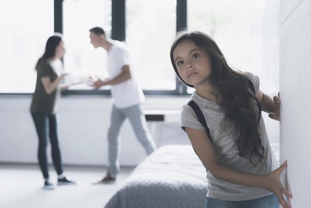 Chica de pelo oscuro escucha a los padres discutiendo en casa