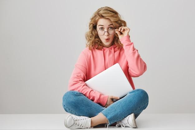 Chica de pelo rizado sorprendida con portátil, mirando emocionado