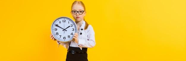Una chica con pelo rojo en un amarillo una chica encantadora en lentes transparentes sostiene un reloj