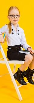 Chica con el pelo rojo. una chica encantadora con gafas transparentes se sienta en una silla blanca y toma notas en un cuaderno.